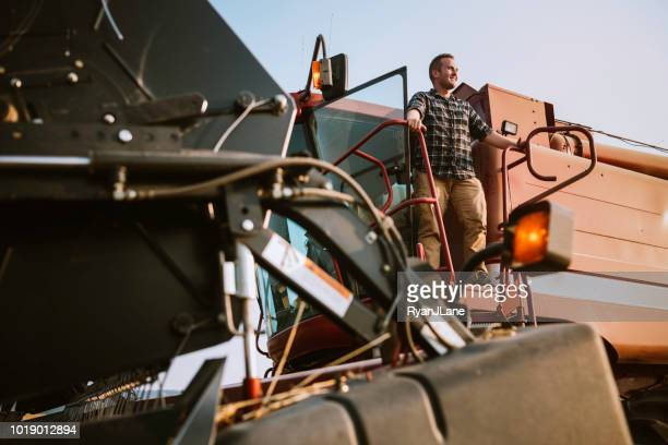farmer standing on combine harvester in idaho wheat field - agricultural machinery stock pictures, royalty-free photos & images