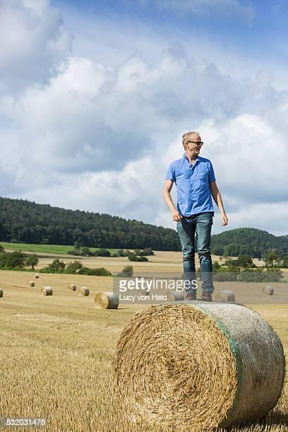 Farmer standing on hay bale in field
