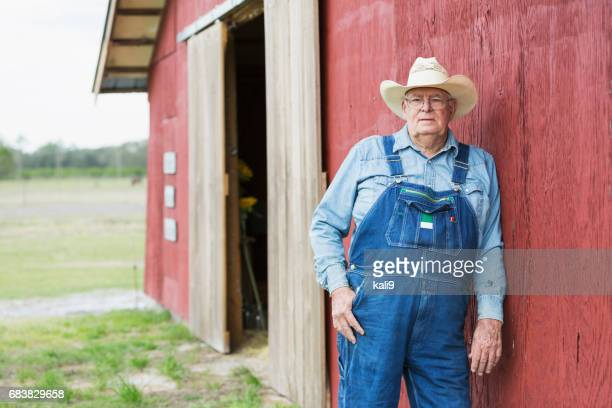 farmer standing outside barn - dungarees stock pictures, royalty-free photos & images
