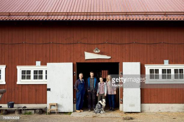 farmer standing with family at doorway of barn - farmhouse stock pictures, royalty-free photos & images
