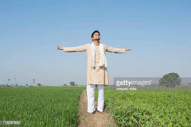 Farmer standing with his arms outstretched in the field, Sonipat, Haryana, India