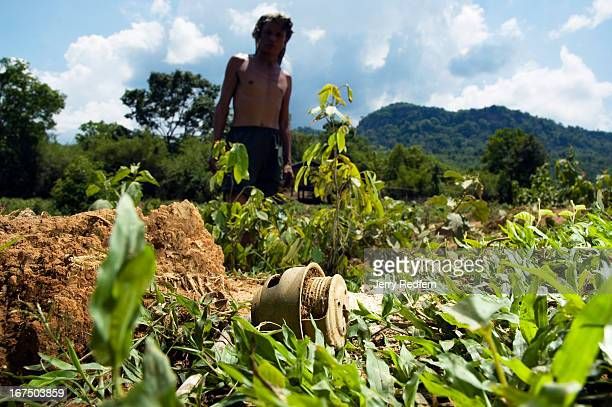 A farmer stands behind a bomb detonator he found in the field behind his home A branch of the Ho Chi Minh Trail once ran through this valley and the...