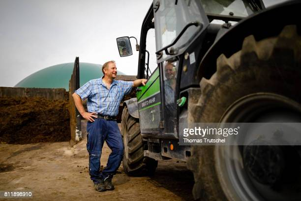 A farmer stands in front of a biogas plant on a farm and talks to a colleague on July 10 2017 in Lanke Germany
