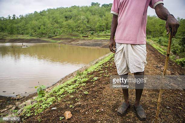 A farmer stands next to a manmade irrigation pond that stores rain water in Dewas Madhya Pradesh India on Monday July 4 2016 Farmers in Dewas...