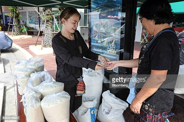 Farmer Suphatson Chanthamon left hands change to a customer at her rice stall in a PTT Pcl gas station in Ubon Ratchathani Thailand on Wednesday Nov...
