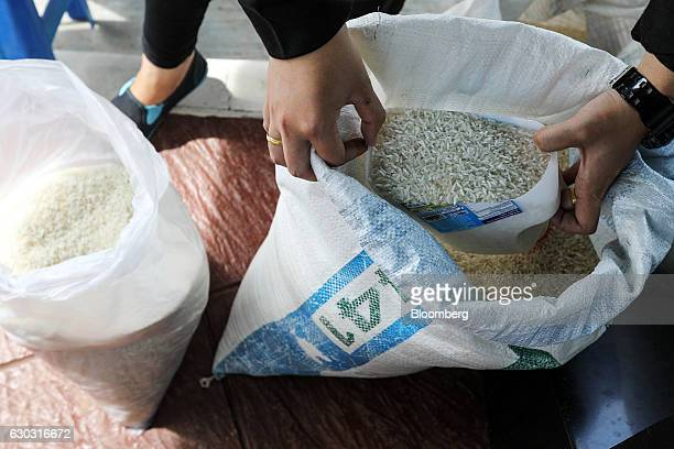 Farmer Suphatson Chanthamon scoops rice from a bag at her stall in a PTT Pcl gas station in Ubon Ratchathani Thailand on Wednesday Nov 9 2016...