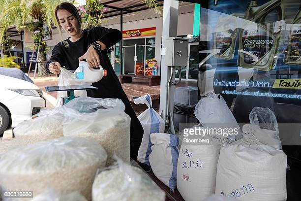 Farmer Suphatson Chanthamon scoops rice into a bag at her stall in a PTT Pcl gas station in Ubon Ratchathani Thailand on Wednesday Nov 9 2016...