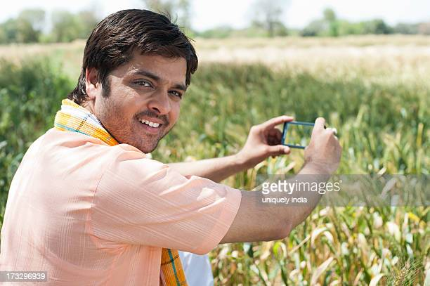 Farmer taking a picture of crop with a mobile phone, Sohna, Haryana, India