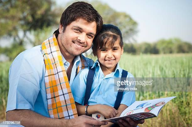 Farmer teaching his daughter and smiling, Sohna, Haryana, India
