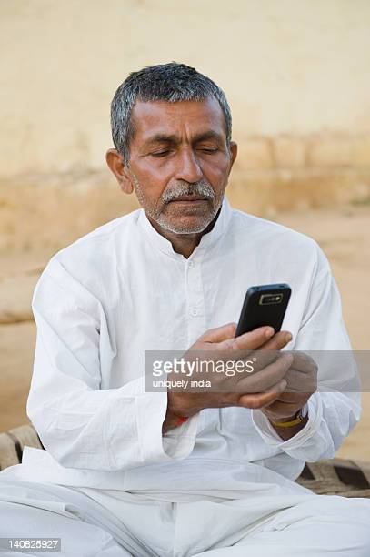 Farmer text messaging on a mobile phone, Hasanpur, Haryana, India