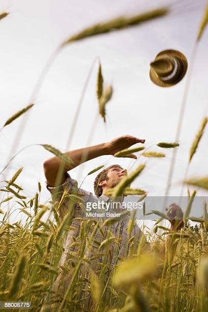 farmer throwing hat in field - sachsen stock-fotos und bilder