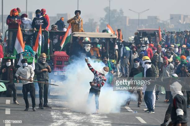 Farmer throws back a tear gas shell fired by the police to disperse them during a tractor rally as farmers continue to demonstrate against the...