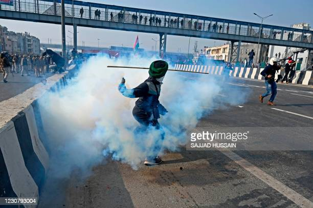 Farmer throws back a tear gas shell towards police during a tractor rally as farmers continue to protest against the central government's recent...