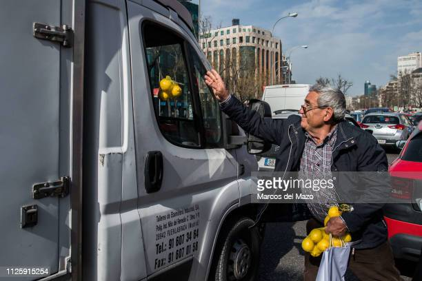 A farmer throws lemons to a truck driver during a protest as they give away citrus to citizens Farmers from all over Spain protest at the...