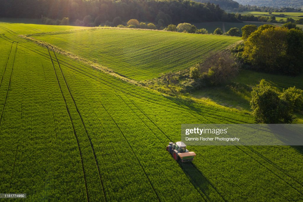 A farmer tills a field with his tractor : Stockfoto