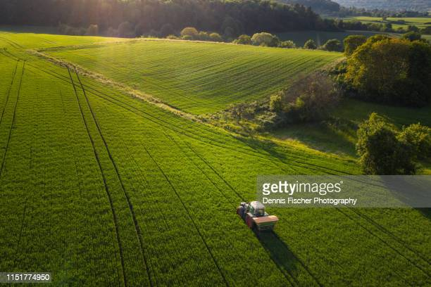 a farmer tills a field with his tractor - landschaft stock-fotos und bilder