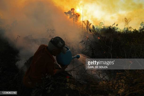 Farmer tries to pour water on an area close to an illegally lit fire in Amazon rainforest reserve, south of Novo Progresso in Para state, Brazil, on...