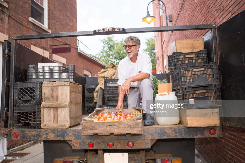 Farmer unloading crates of organic tomatoes outside grocery store : Stock Photo