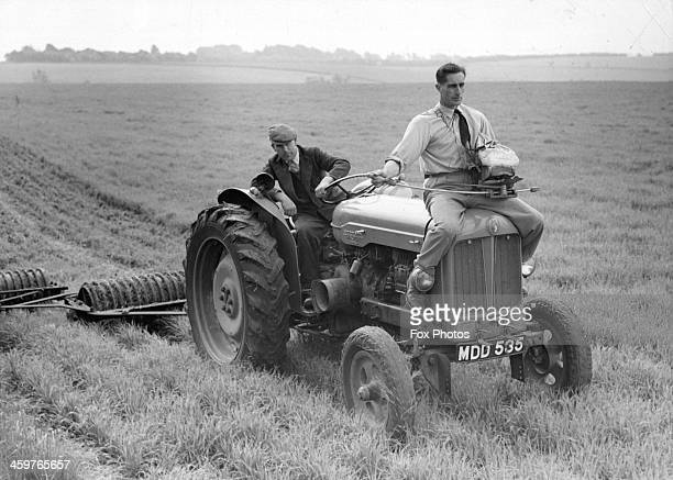 A farmer uses a fiddle broadcaster on top of a tractor to sow grass seeds on a farm in Gloucester England June 121958