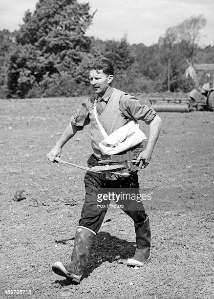 A farmer uses a fiddle broadcaster to sow grass seeds on a farm in Gloucester England May 121861