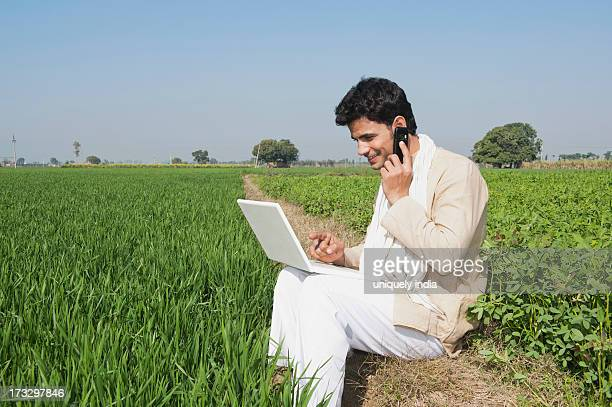 Farmer using a laptop and talking on a mobile phone in the field, Sonipat, Haryana, India