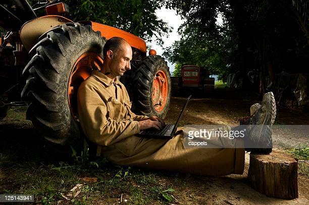 Agricultor com um Laptop em seu Farmyard.Color imagem