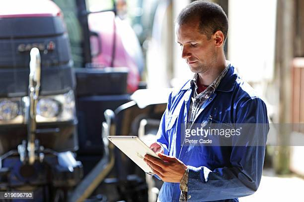 Farmer using a tablet . Tractor and farm .
