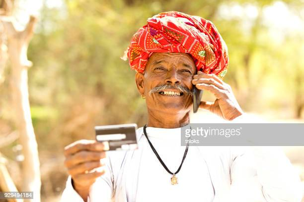 Farmer using credit card and mobile phone