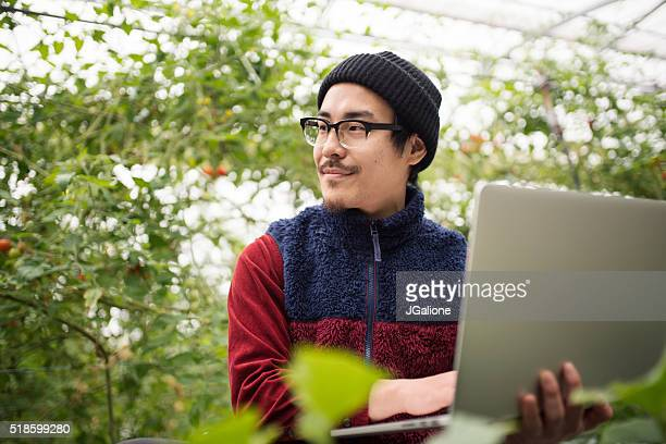 farmer using laptop computer to conduct research in a greenhouse - jgalione stock pictures, royalty-free photos & images
