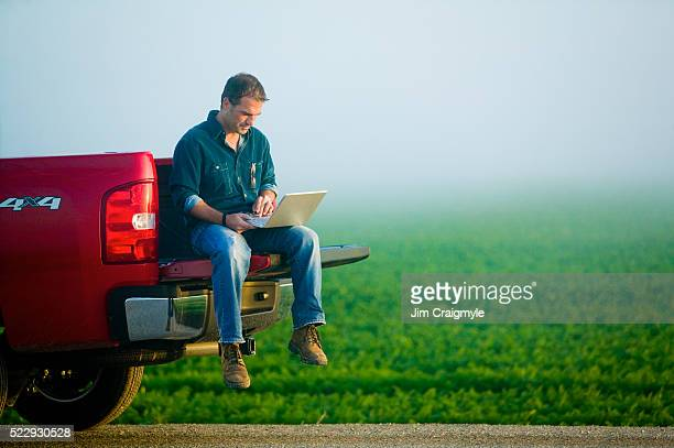 farmer using laptop from tailgate of truck - jim farmer stock photos and pictures
