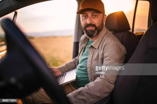 Agricultores utilizando la computadora portátil en su coche