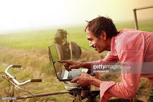Farmer using laptop in the field