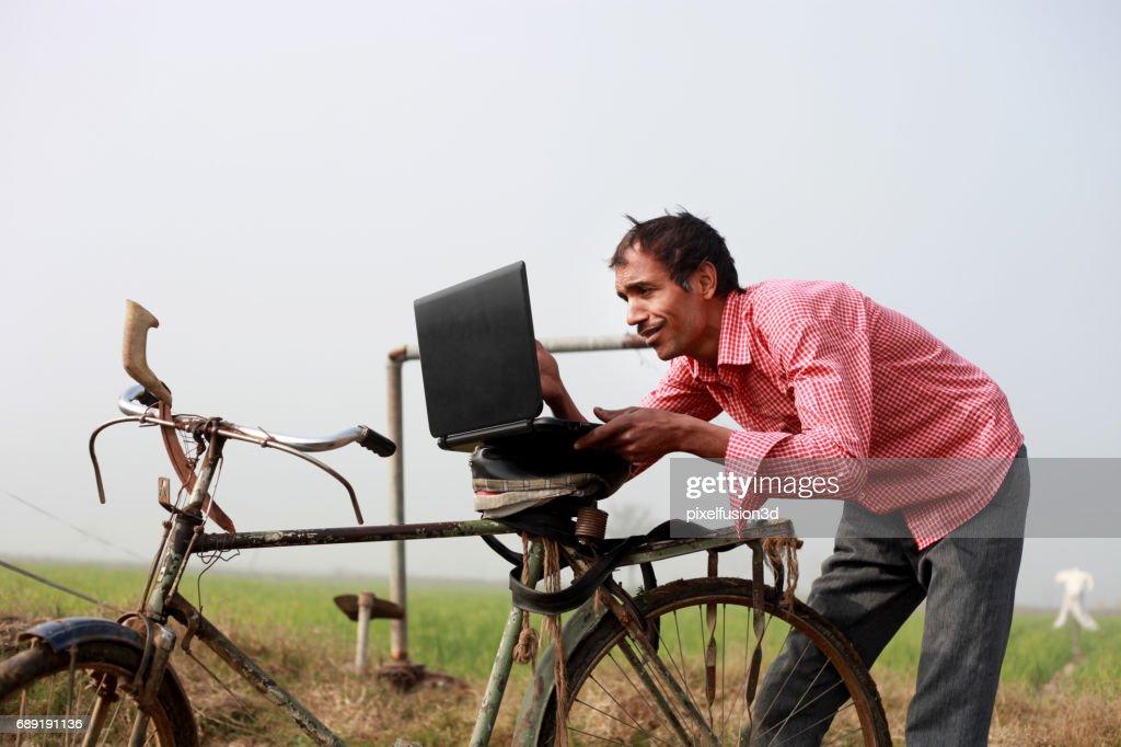 Granjero usando una computadora portátil en el campo : Foto de stock