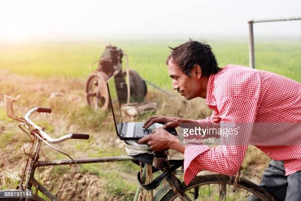 Farmer using laptop in the field