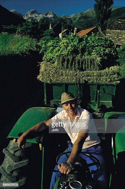 Farmer Valley of Aisa Huesca A farmer posing in their tractor with the picked up crop To the bottom the Pyrenees