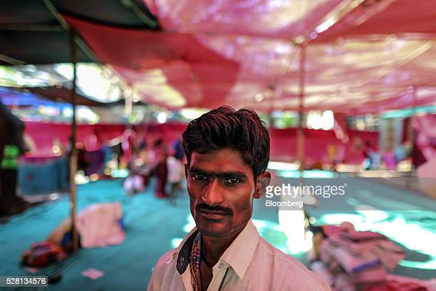 Farmer Vijay Jadhav stands for a photograph inside a temporary suburban camp set up by local political party Shiv Sena for the rural poor traveling...