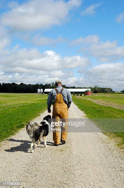 Farmer walking to the barn with his dog