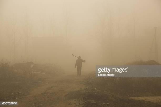 Farmer walks at suburbs in heavy smog on December 31, 2016 in Beijing, China. Beijing Meteorological Bureau has issued an orange alert for heavy smog...