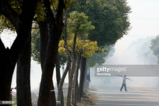 A farmer walks on a road located at the site of a future Walt Disney Co theme park in Shanghai China on Friday Nov 6 2009 Walt Disney's newest castle...