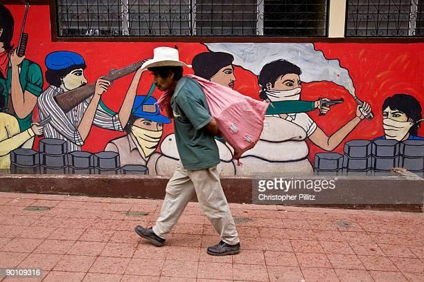 A farmer walks past a Sandinista war mural in Jinotega