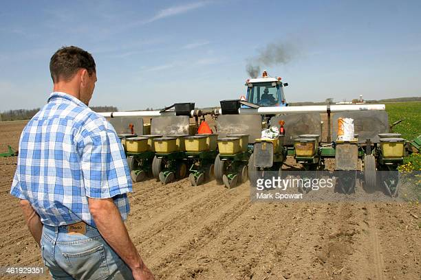Farmer watches as his field starts to be planted for the upcoming growing season.