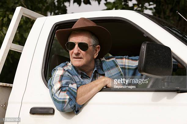 Farmer wearing sunglasses looking out of vehicle