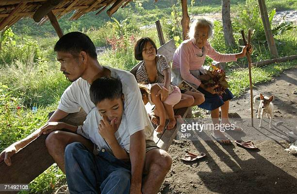 Farmer Wilfredo Azures along with three of his five children Alfred Giselle holding two years old Joy and their grandmother Petra Cariso look out...