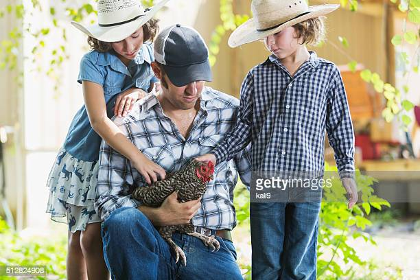 Farmer with children on family farm holding chicken