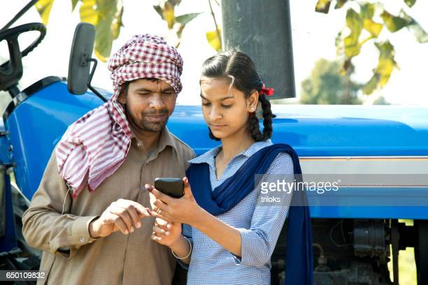 farmer with daughter using mobile phone - village stock pictures, royalty-free photos & images