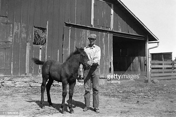 farmer with foal in barnyard 1935, retro