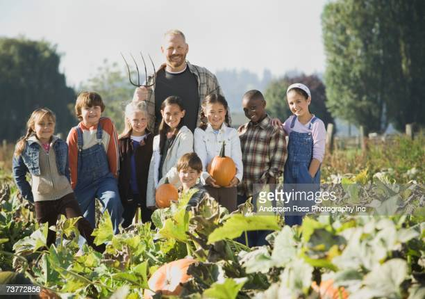 Farmer with group of children in pumpkin patch