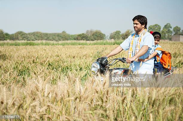 Farmer with his daughter riding a motorcycle in the field, Sohna, Haryana, India