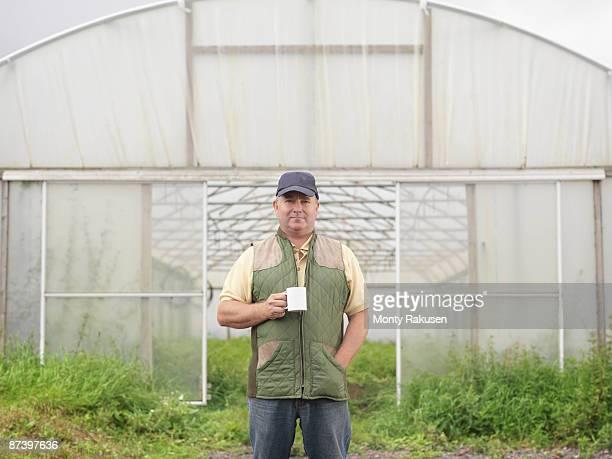 Farmer With Mug Outside Polytunnel