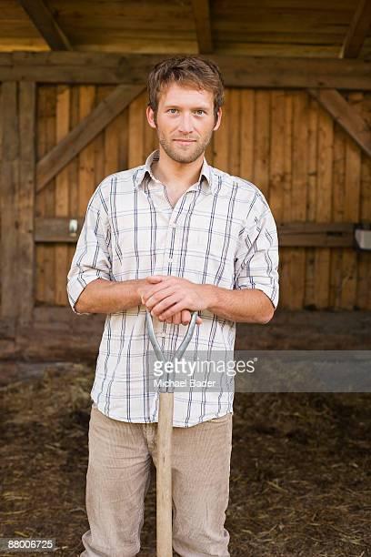 Farmer with pitchfork in barn, smiling, portrait